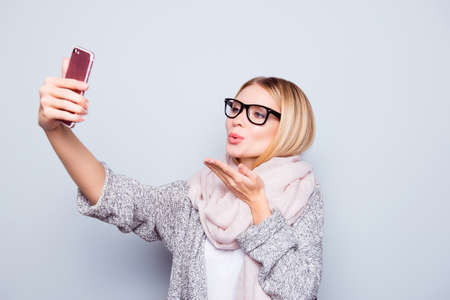 Beautiful charming lady in spectacles dressed in warm outfit is sending ari-kiss and taking selfie  on her cellphone. She is isolated on grey background 免版税图像