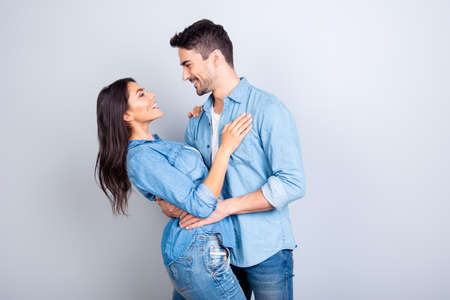 This sweety love makes my head spin! Handsome joyful happy man in casual clothes is hugging her girlfiend's waist, isolated on grey background Stockfoto
