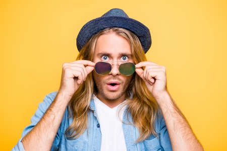 Really? Close up portrait of shocked bearded blond attractive guy holding glasses with fingers, amazed with open mouth, looking over glasses, standing over yellow background