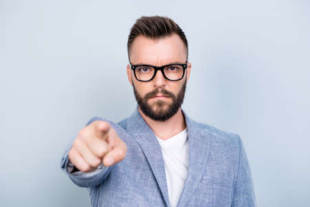 You! Strict handsome bearded brunet man is choosing you, pointing at the screen, wearing formal outfit, on a pure light background, harsh and severe Stock Photo