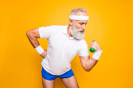 Body care, hobby, weight loss lifestyle. Cool grandpa with confident grimace exercising holding equipment up, lifts it with strength and power, wearing blue sexy shorts, show legs