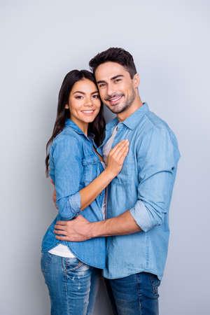 영원히 함께! 청바지 캐주얼 옷을 입고 행복 신혼 부부의 세로 사진, 그들은 웃 고, 포옹 하 고 회색 배경에 고립 된