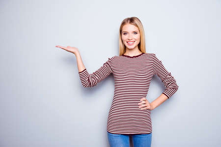 I recommend you to buy it! Beautiful, confident and happy young woman dressed in casual outfit is pointing on empty space over  her palm, she is isolated on grey background
