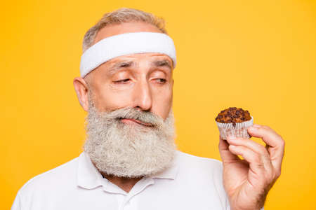 Athlete cool uncertain unsure ponder fit picky grandpa holds forbidden tasty yummy treat, decides. Weightloss, healthcare, restriction, question, thoughts, workout, gym, regime, bodycare