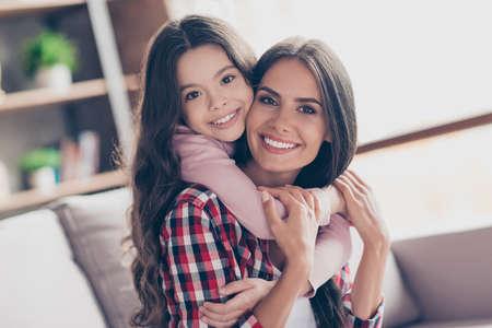 Tijd van tederheid. De mooie jonge glimlachende mamma en haar kleine preteen dochter brengen samen tijd door. Ze knuffelen en spelen thuis