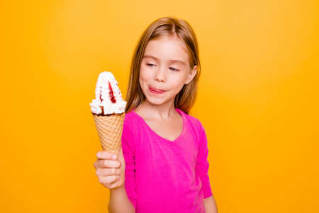 Close up portrait of beautiful, cute, little lady, holding ice cream in waffle cone in her hand, looking hungry at ice cream, licking her lips with tongue, standing over yellow background Stock Photo