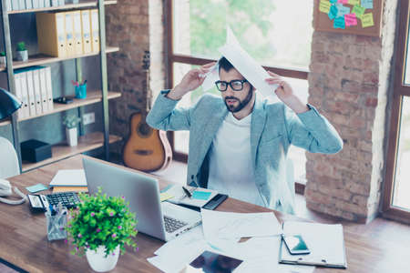 Portrait of young, excited accountant under stress from too much work in the workstation, holding papers in hands, closing his head with papers, he worries that he will not ready with report in time