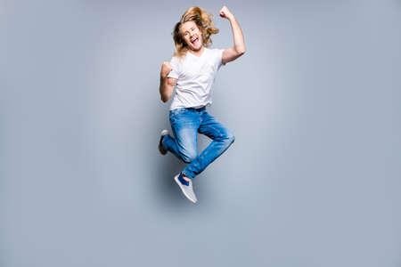 ブロンドの長い髪を持つ喜びの幸せな興奮した若者は叫び、灰色の背景に孤立した上げ拳でジャンプしています 写真素材