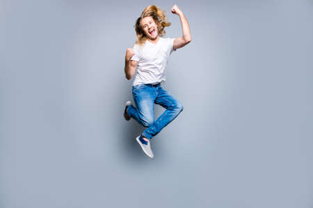 Joyful happy excited young man with blonde long hair is screaming and jumping up with raised fists, isolated on grey background Stock fotó - 90378176
