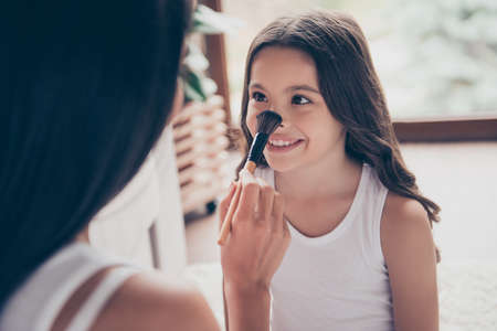 Close up portrait of beautiful smiling little girl with long dark hair, her mother is applying doing make up and applying powder on her nose using a brush, they are having fun Stock Photo