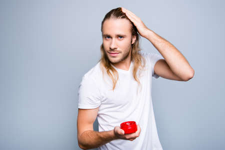 Portrait of confident happy smiling young guy with bristle, he is holding red jar with gel and applying gel on his long blonde clean hair, isolated on grey background Imagens