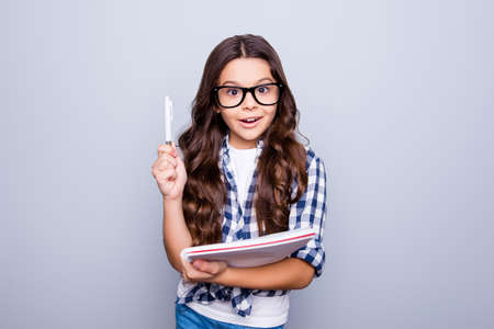 Portrait of little, brunette, cute, smiling girl holding notebook raising her pencil up, finding a solution how to do exercise, standing over grey background