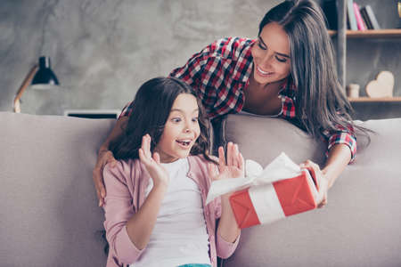 Dreams come true on birthday! Here you are a present! Young charming mother in casual clothes is giving a red gift box to her surprised and cheerful little princess Stockfoto