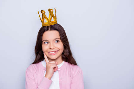 Close up portrait of little caucasian cute girl with crown on head looking up holding forefinger near face dreaming to be a queen while standing over grey background