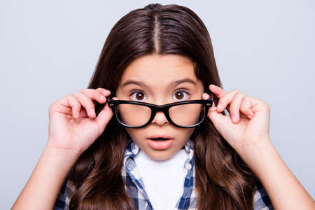 Close up portrait of shocked, unbelievable, little girl looking over glasses with wide opened eyes and mouth, holding glasses with hands, standing over grey background Stockfoto