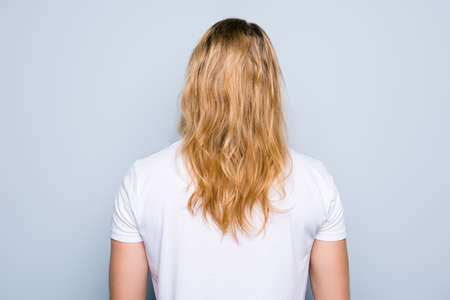 Back view portrait of young man clothed in white tshirt, he has perfect, shiny blonde long healthy hair, isolated on grey background Stock Photo