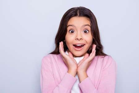 Cerca de una niña sorprendida, atractiva y adorable, abrió la boca y los ojos, sosteniendo sus brazos cerca de las mejillas, sobre un fondo gris. Foto de archivo - 90377235