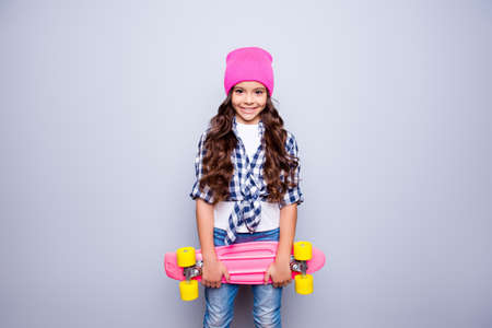 Portrait of little cute smiling girl with pink skate-board in pink hat who is ready to ride on the street standing over grey background