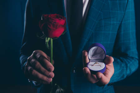 Close up shot of man in formal wear, holding in one hand box with engagement ring and rose in another one. Will you marry me? Foto de archivo