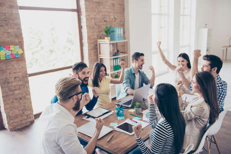 Close up of successful team of business partners with raised up hands in light modern workstation, celebrating the growth of the income