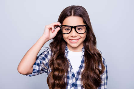 Closeup portrait of smart attractive little girl in checkered shirt  holding her spectacles  smiling looking to the camera standing over grey background Stockfoto