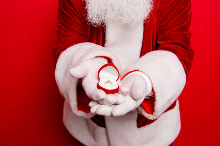 Marriage propose from santa. Will you marry me? Close up shot of white bearded santa  presenting wedding  gold ring in the box, standing over red background Stock Photo