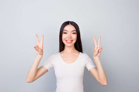 Portrait of glad, funny, smiling, toothy, beautiful girl showing with two hands v-sign, two peace symbols, standing over grey background Archivio Fotografico