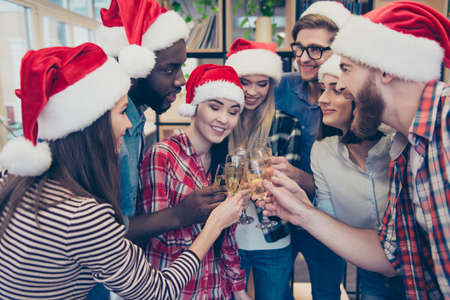 Close up portrait of mixed race, multi national businessmen and businesswoman, joyful bearded employers and beautiful entrepreneurs, toasting their glasses with champagne, enjoying christmas corporate, party makers in the campus