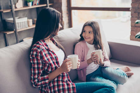 Adorable cute smiling young schoolgirl is holding a cup of cacao, sitting on a couch and telling her mum about school news