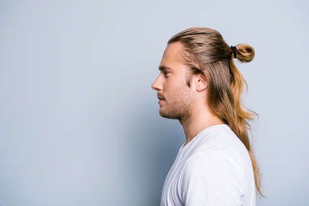 Close up side view photo of serious confident young guy, he has hair bun, isolated on grey background Reklamní fotografie - 90710905
