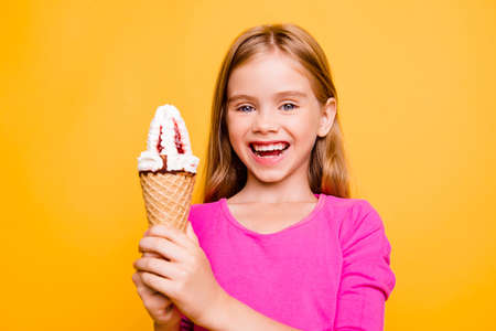 Close up portrait of very happy, blonde, little lady holding delicious ice cream in waffle cone in two hands, looking at camera, standing over yellow background