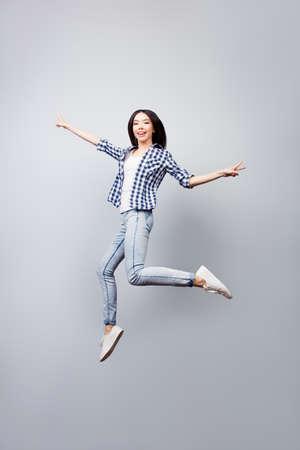Das schöne frohe Mädchen, das im karierten Hemd und in den Jeans gekleidet wird, ist jumpig oben und zeigt Vzeichen, sie wird auf grauem Hintergrund lokalisiert