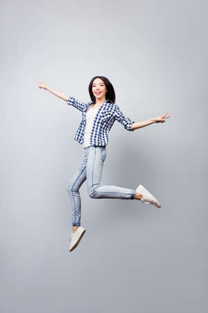 Beautiful joyful girl dressed in checkered shirt and jeans is jumpig up and showing v-sign, she is isolated on grey background Standard-Bild