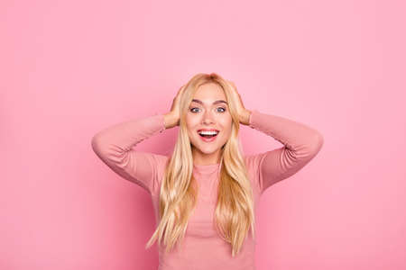 Happy excited young astonished surprised lovely pretty woman in pink clothes. She is touching her head because she can't believe her eyes looking at sales, isolated on vivid pink background
