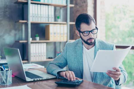 Portret młodego, poważnego księgowego trzymającego w ręku dokumenty i podsumowującego rachunki firmy za ostatni miesiąc, siedząc przy biurku na stanowisku roboczym
