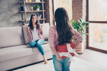 Concept of mothers day. Little girl is hiding a red giftbox behing her back, surprised cheerful happy mother is sitting on a couch on the background