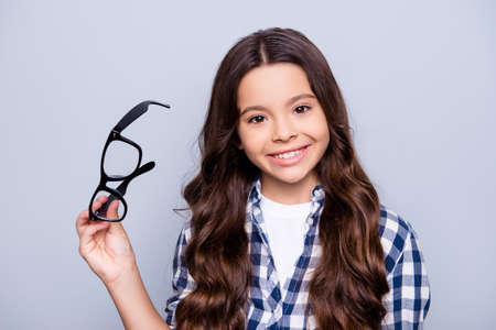 Close up portrait of beautiful, charming, little girl taking out glasses and using lenses, smiling to the camera standing over grey background Stockfoto