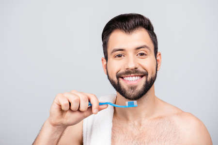Close up portrait of toothy, attractive man cleaning his white teeth, holding a teeth brush in hand, having beaming smile, standing over grey background