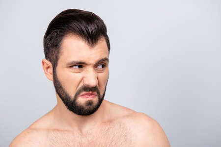 Close up portrait of emotional man with dislike emotion on his face, looking to the side, standing over grey background Stok Fotoğraf