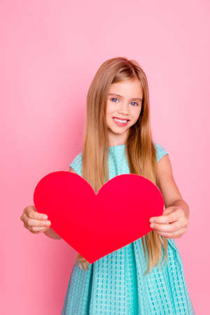 Love, happiness, people, mother day concept. Smiling caucasian little lady holding red heart, presenting gift card for her mother, standing over pink background