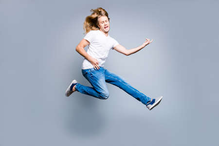 Excited and amazed young guy with blonde long hair in casual clothes is celebrating his victory, he is playing an imaginary guitar, isolated on grey background Stock Photo