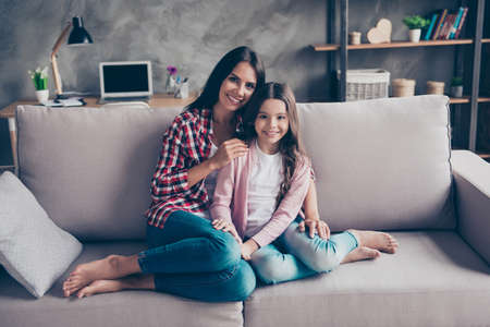 So nice and admirable sweet tender family portrait! Charming cheerful mom and her cute kid are hugging and sitting on a sofa at home