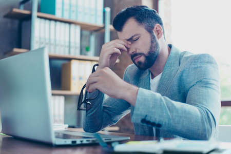 Portrait of attractive young IT person, employee taking off his spectacles, having eyes hurt, having his eyes closed, holding his fingers on nose between eyes, looking tired, overworked