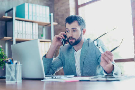 Brunet, attractive, young banker with bristle, in formal jacket talking on the smartphone, he is  annoyed, displeased, having conflict with client during telephone conversation, sitting at his desktop