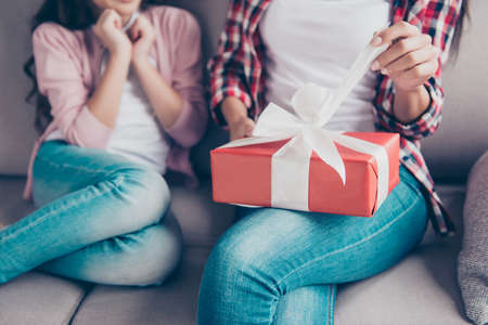 Cropped close up photo of womans hands unpacking red gift box on her knees, she is touching white ribbon, her little daughter is waiting for mothers reaction