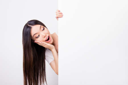 Copyspace portrait of charming  amazed asian woman hiding, standing behind empty white vertical wall, putting her palm on her cheek, opened her mouth, looking at   empty white vertical wall while standing over white background