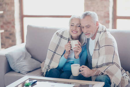 It is almost winter, so cold outside, but so sweet time we spend together! Happy cheerful peaceful couple of pensioners are resting,  relaxing, hugging, drinking tea with closed eyes at the weekend