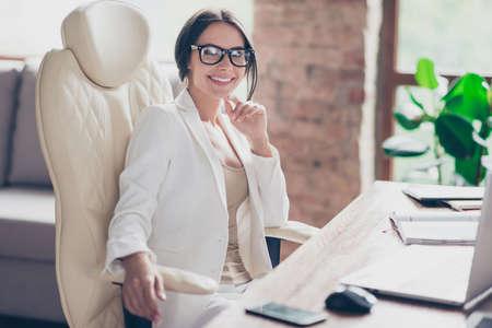 현대 사무실에서 바탕 화면에 앉아있는 유명한 유명한 성공적인 자신감 웃는 전문 매력적인 비즈니스 아가씨의 초상 스톡 콘텐츠