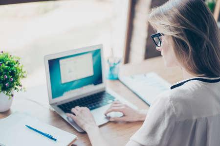 Cerca de la foto de una periodista joven pero profesional, ella está mirando el monitor y escribiendo un artículo para una revista.