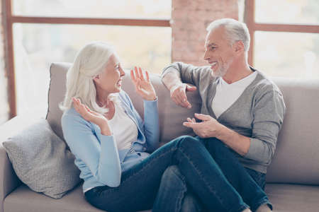 Happy senior couple having fun, looking to each other, laughing, sitting in living room, womans legs lying on mans knees, couple expressing their emotion with hands Stock Photo